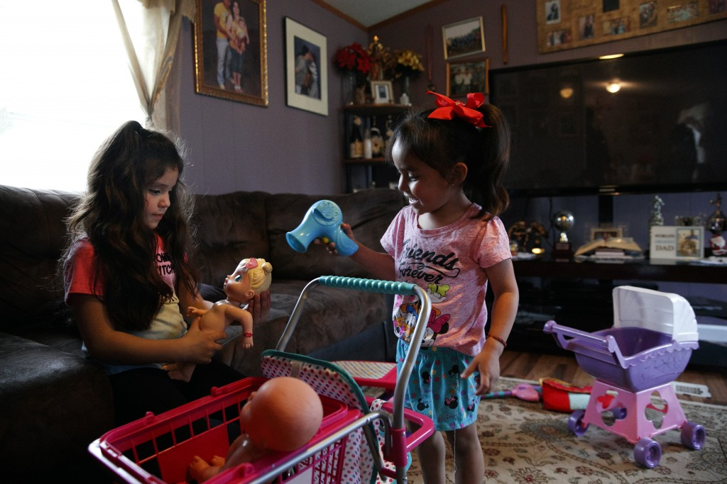 Alexa Montoya, 5, left, and Kimberly Rivera, 3, play with dolls as Kimberly's mother registers to vote during a voter registration in a largely Latino...