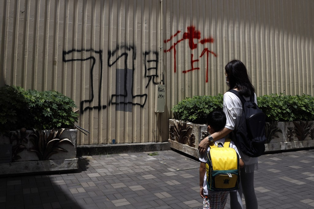 """Pamela Lam and her son stand in Hong Kong, Friday, July 3, 2020. Lam's 6-year-old son fell in love with the Hong Kong protest anthem, """"Glory to Hong K..."""