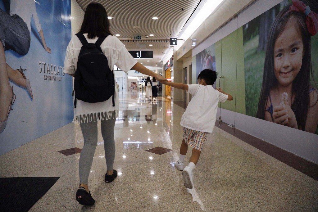 Pamela Lam plays with her son on the way to school in Hong Kong, Friday, July 3, 2020. Lam's 6-year-old son fell in love with the Hong Kong protest an...