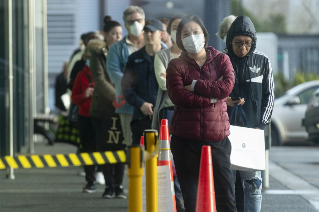 People queue early morning outside a supermarket in Hobsonville, Auckland, as New Zealand prepares to move into Covid-19 Alert Level 3, Wednesday, Aug...