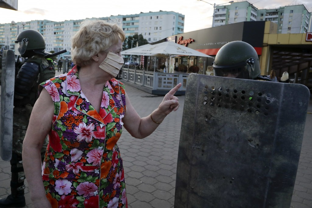 A woman gestures as she talks with riot police officers in the capital of Minsk, Belarus, Tuesday, Aug. 11, 2020. Heavy police cordons blocking Minsk'...