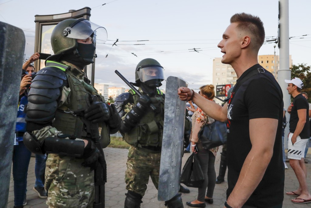 A man talks with riot police officers as they block a part of a street in the capital of Minsk, Belarus, Tuesday, Aug. 11, 2020. Heavy police cordons ...