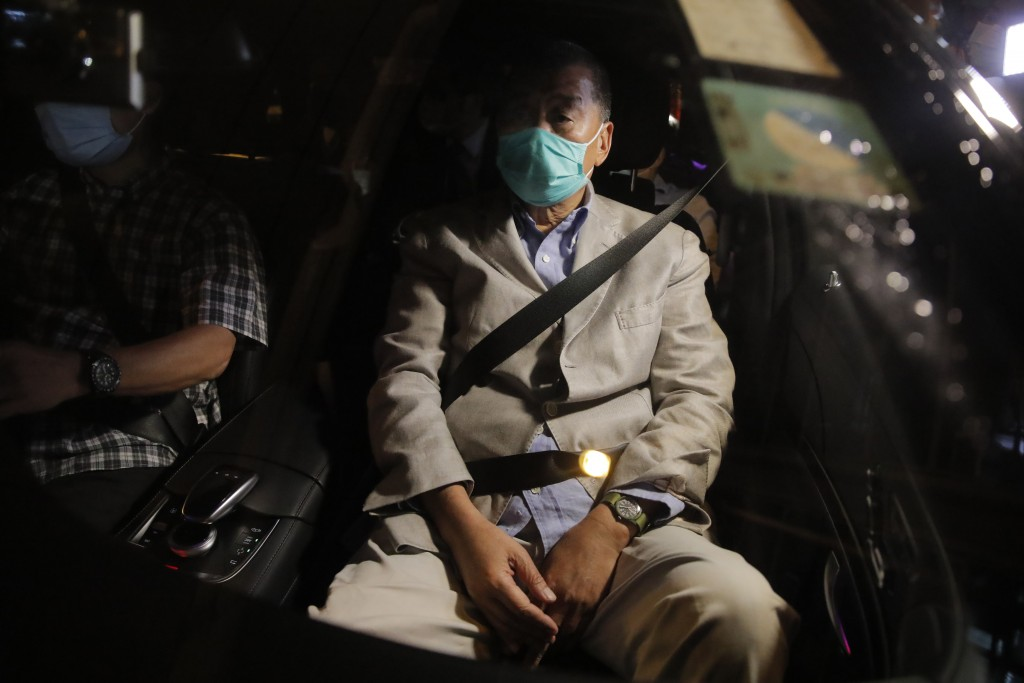 Hong Kong media tycoon and newspaper founder Jimmy Lai, sits in a car as he leaves a police station after being bailed out in Hong Kong, Wednesday, Au...