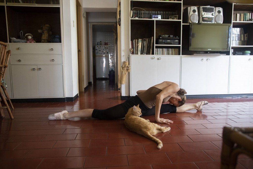Carolina Wolf, who dances with Venezuela's national ballet, stretches at the end of her training session in her living room, during a lockdown to curb...