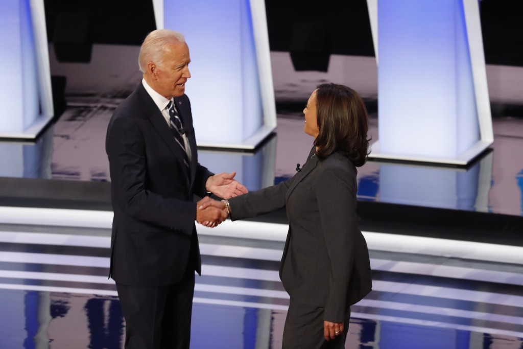 FILE - In this July 31, 2019, file photo, fFormer Vice President Joe Biden shakes hands with Sen. Kamala Harris, D-Calif., before the second of two De...