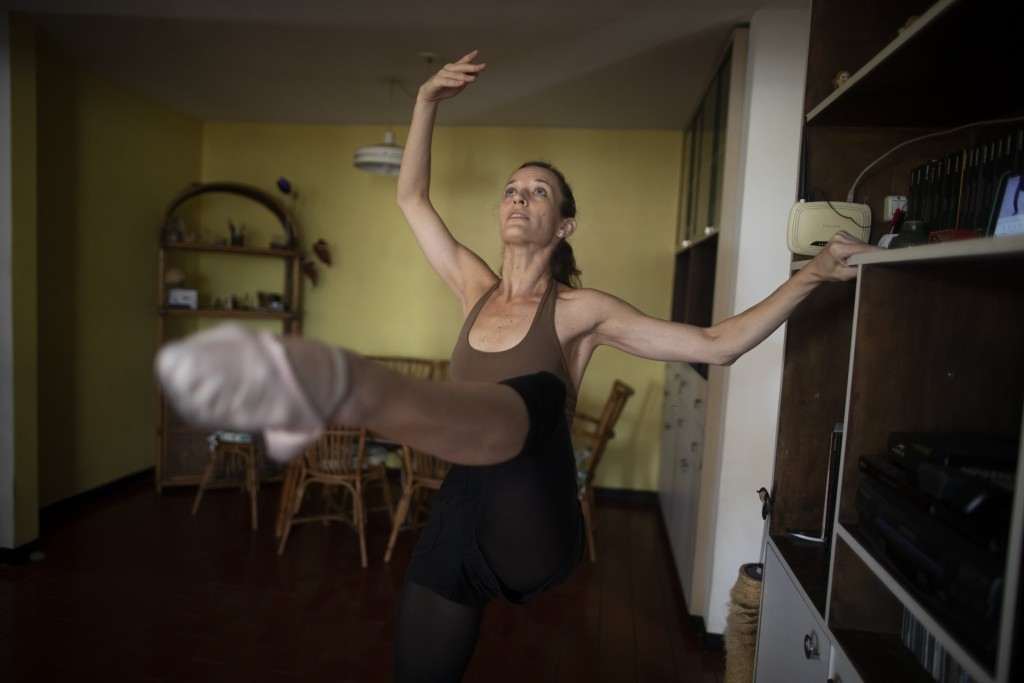 Carolina Wolf, who dances with Venezuela's national ballet, trains in her living room during a lockdown to curb the spread of COVID-19 in Caracas, Ven...