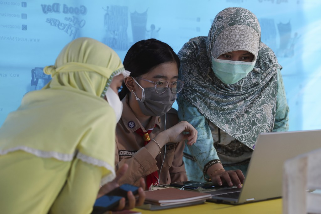 A mother, right, and her daughter, center, wear face masks to help curb the spread of the new coronavirus as they use free wifi to access an online le...