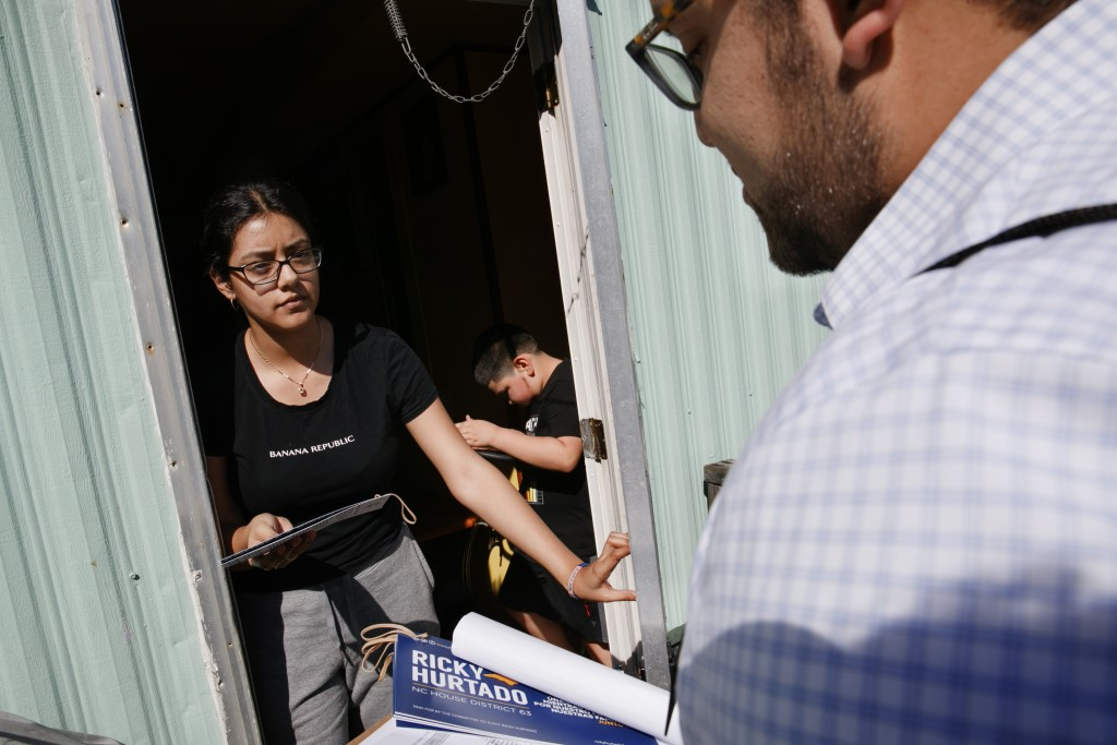 Evelyn Lara, 19, with her brother Iker, 7, opens the door as Ricky Hurtado, a Democratic candidate for the North Carolina state house, canvasses voter...