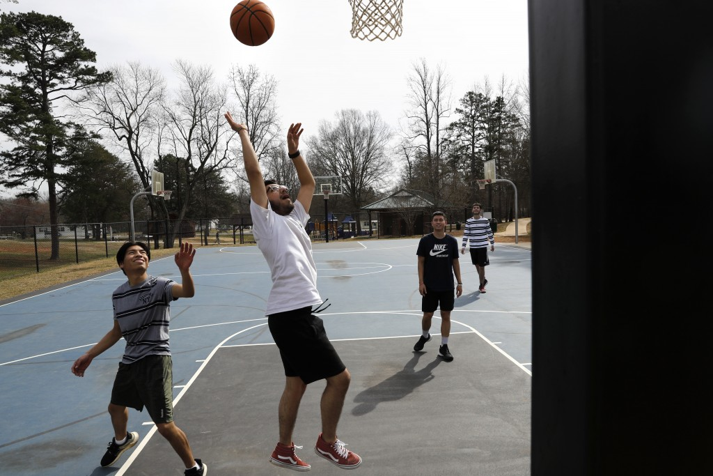 John Paul Garcia, 20, center, plays basketball with friends from the community college that they attend, Allan Berduo, 19, left, Duncan Syhachack, 19,...