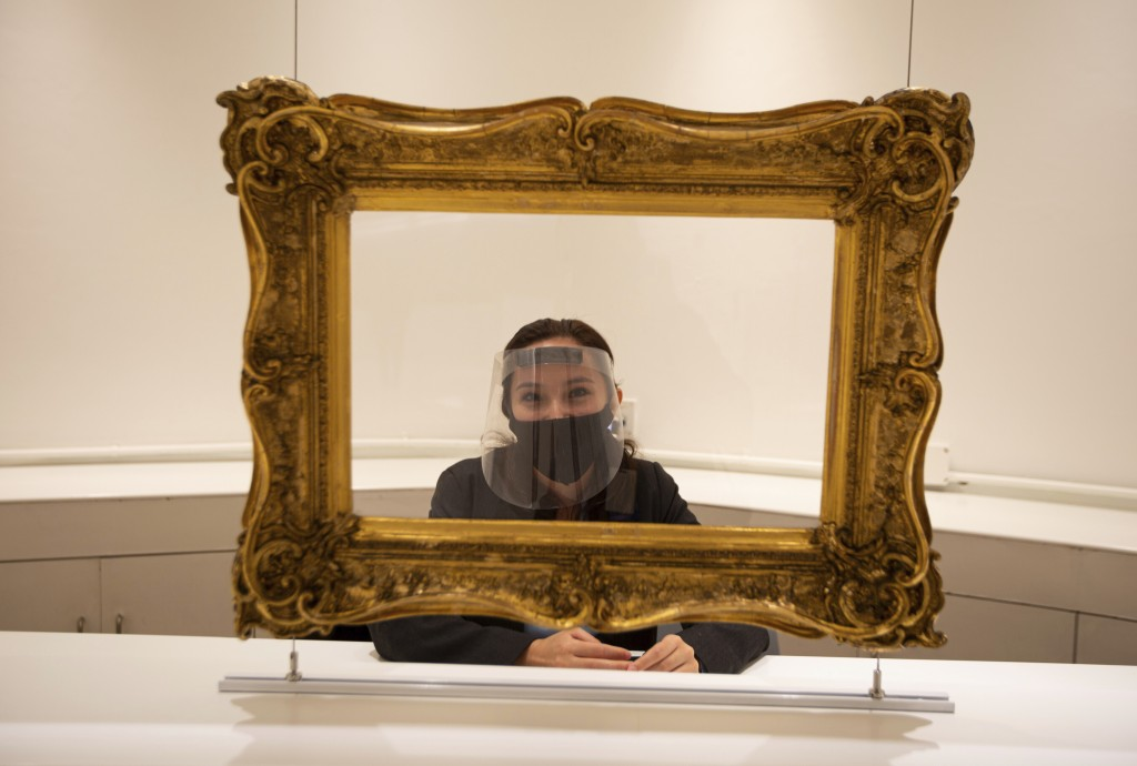 Wearing a face shield and mask, and standing behind a framed protective shield to curb the spread of the new coronavirus, Sofia Velasquez waits for vi...
