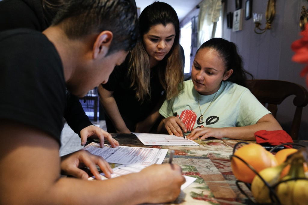 Claudia Bahena, 21, of Burlington, N.C., right, is helped to register to vote during a voter registration drive by community activists, in Burlington,...