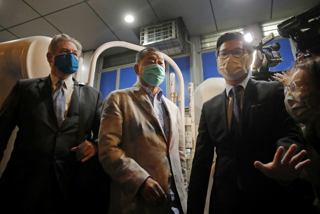 Hong Kong media tycoon and newspaper founder Jimmy Lai, center, walks out from a police station after being bailed out in Hong Kong, Wednesday, Aug. 1...