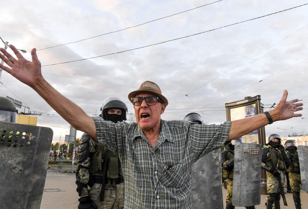 An elderly man gestures trying to stop police officers who detain opposition supporters protesting the election results as protesters encounter aggres...