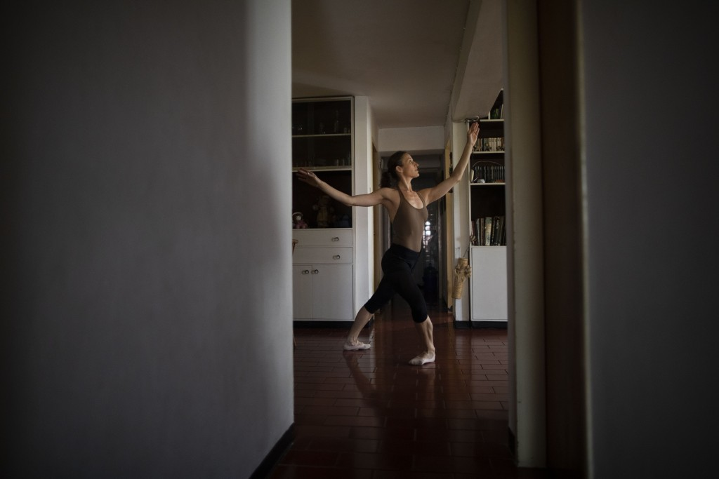 Carolina Wolf, who dances with Venezuela's national ballet, trains in her living room, during a lockdown to curb the spread of COVID-19 in Caracas, Ve...
