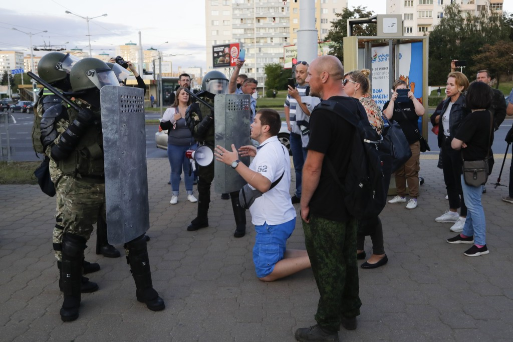 A man on his knees talks with riot police officers in the capital of Minsk, Belarus, Tuesday, Aug. 11, 2020. Heavy police cordons blocking Minsk's cen...