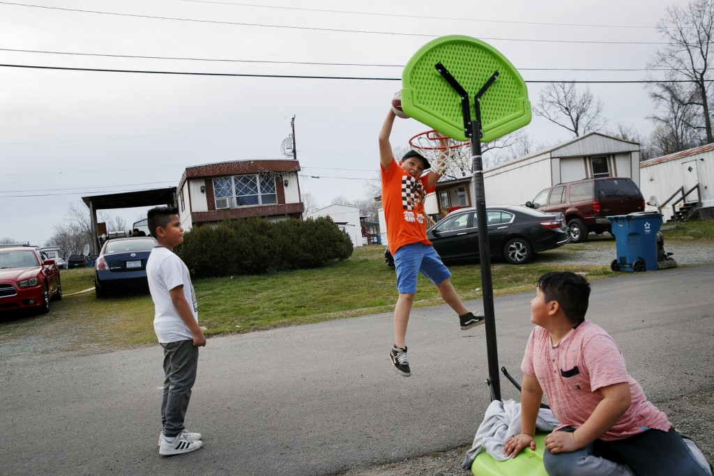 Sebastian Cervantes, 9, left, watches as Marvin Montoya, 10, makes a basket, next to Irvin Bahena, 10, in Burlington, N.C., Wednesday, March 11, 2020,...