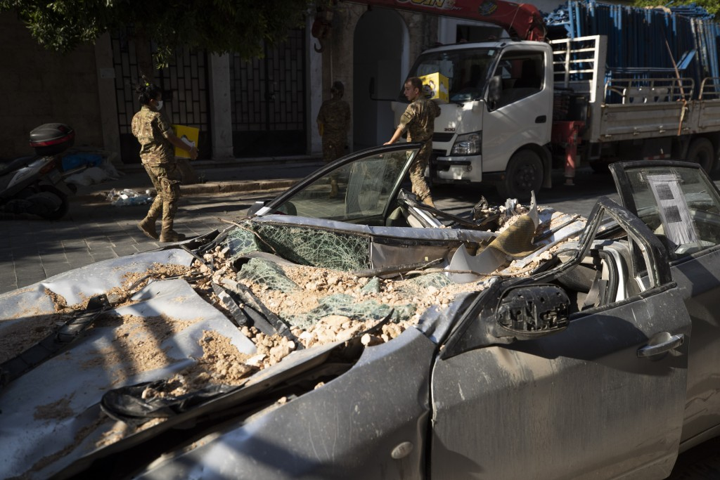 Lebanese army soldiers hold aid boxes past a destroyed car near the scene of last week's explosion that hit the seaport of Beirut, Lebanon, Wednesday,...