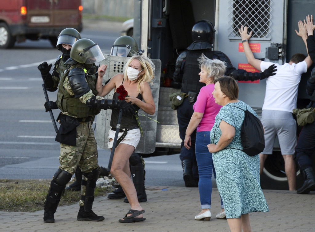 A woman fights with a police officer as the other police officers detain an opposition supporter protesting the election results as protesters encount...