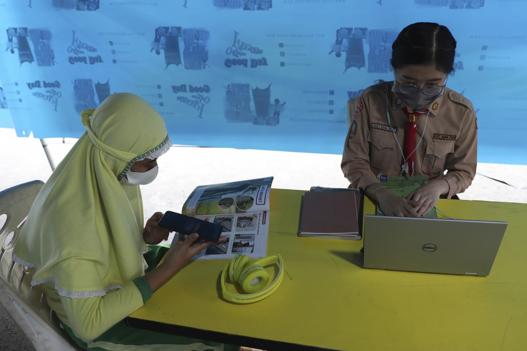 Students wear face masks to help curb the spread of the new coronavirus as they use free wifi to access an online lesson inside a temporary tent in Ja...