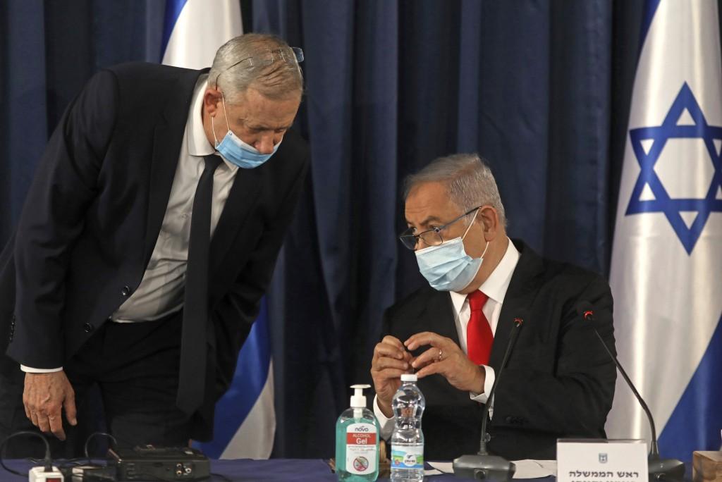 FILE - In this June 7, 2020 file photo, Israeli Prime Minister Benjamin Netanyahu, right, speaks with Defense Minister Benny Gantz, both wearing prote...