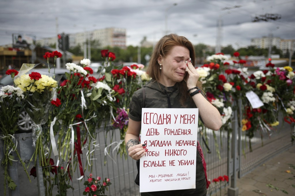 """Alina Krus, 26, holds a poster at the place where a protester died amid the clashes in Minsk, Belarus, Wednesday, Aug. 12, 2020 saying """"It's my birthd..."""