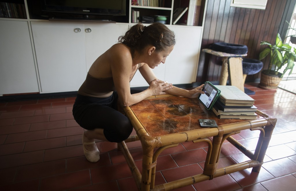 Carolina Wolf, who dances with Venezuela's national ballet searches her tablet for a youtube video by Ernst Meisner from the Dutch national ballet bef...