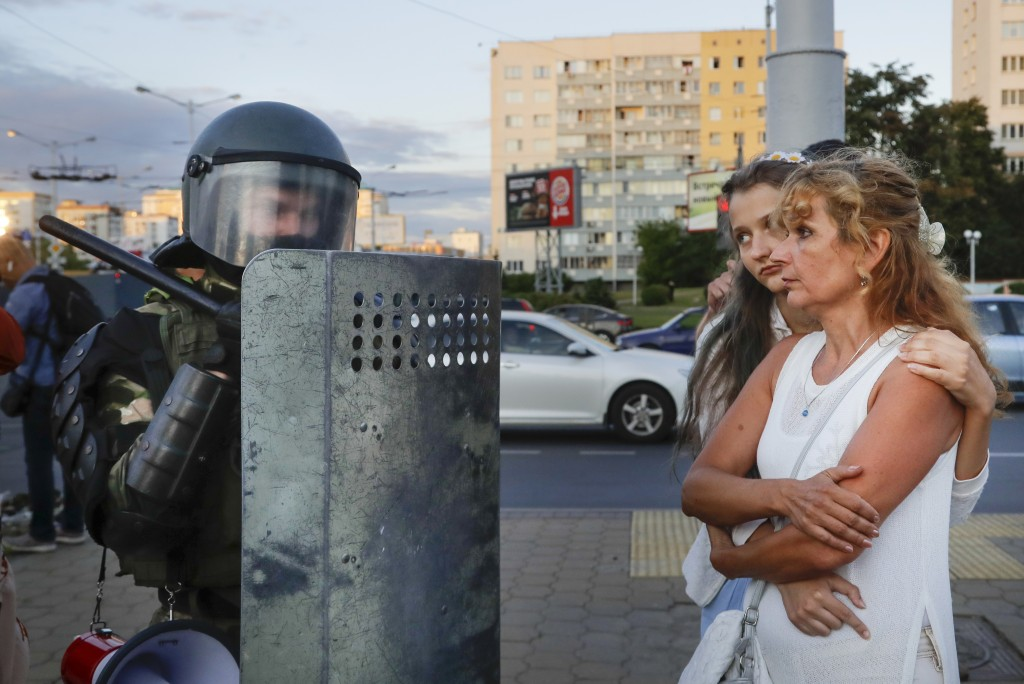 Two women talk with a riot police officer as police block a part of a street in the capital of Minsk, Belarus, Tuesday, Aug. 11, 2020. Heavy police co...