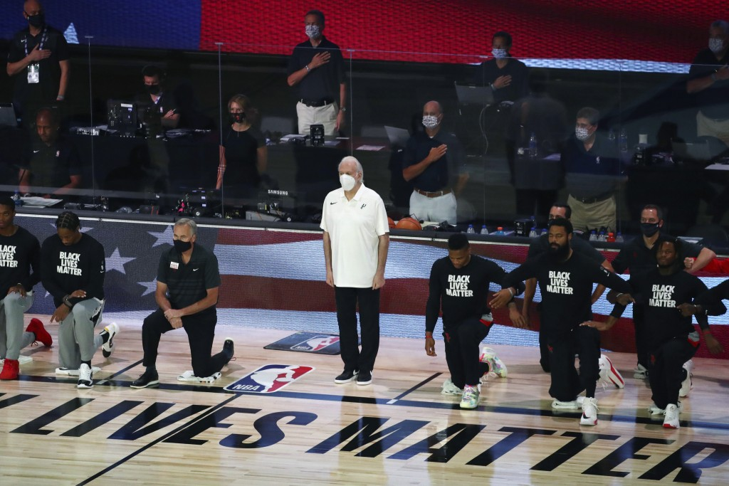 San Antonio Spurs head coach Gregg Popovich, standing at center, wears a mask while players kneel before an NBA basketball game against the Houston Ro...