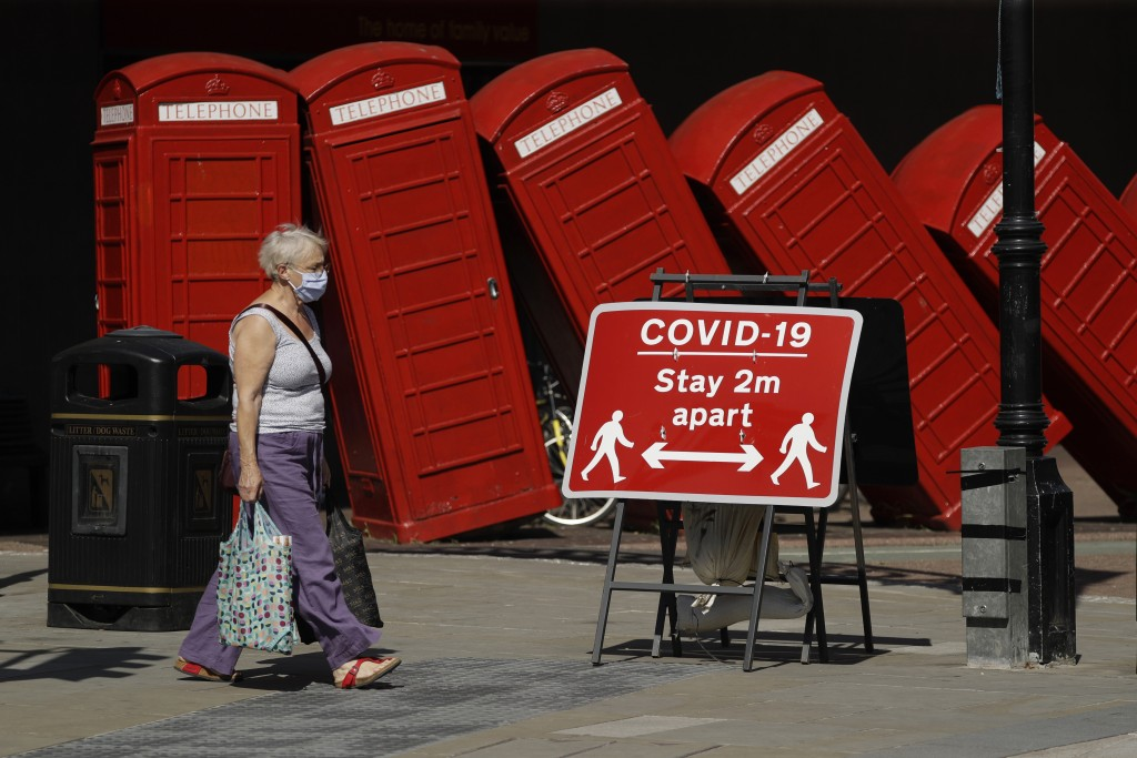 FILE - In this file photo dated Monday, June 22, 2020, a sign requesting people stay two metres apart to try to reduce the spread of COVID-19 is displ...