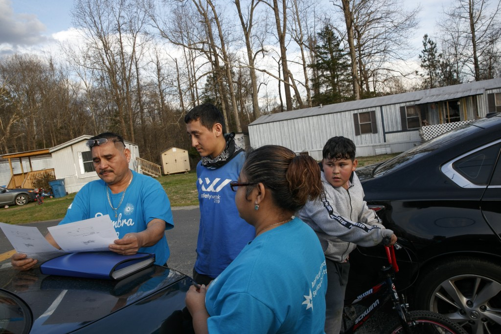 Prisi Hernandez, left, and Laura Hernandez, both with the organization Siembra NC, help Nery Ocampo, 19, center, to register to vote, as Irvin Bahena,...