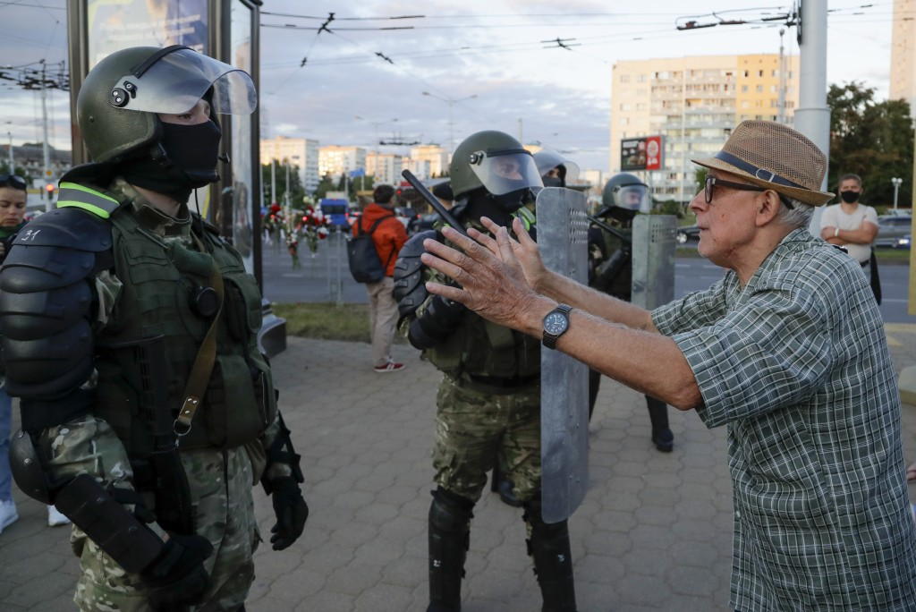 A elderly man gestures as he taks with riot police officers in the capital of Minsk, Belarus, Tuesday, Aug. 11, 2020. Heavy police cordons blocking Mi...