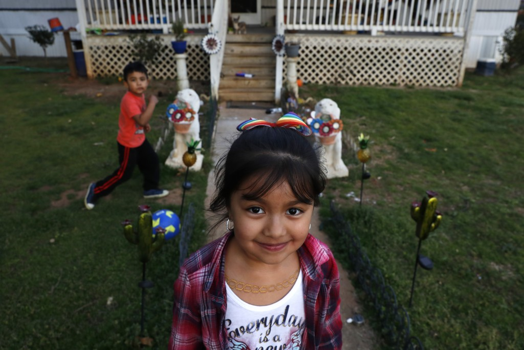 Dulce, 6, and her brother play in the yard of their family home across the railroad tracks in Burlington, N.C., Monday, March 9, 2020. (AP Photo/Jacqu...