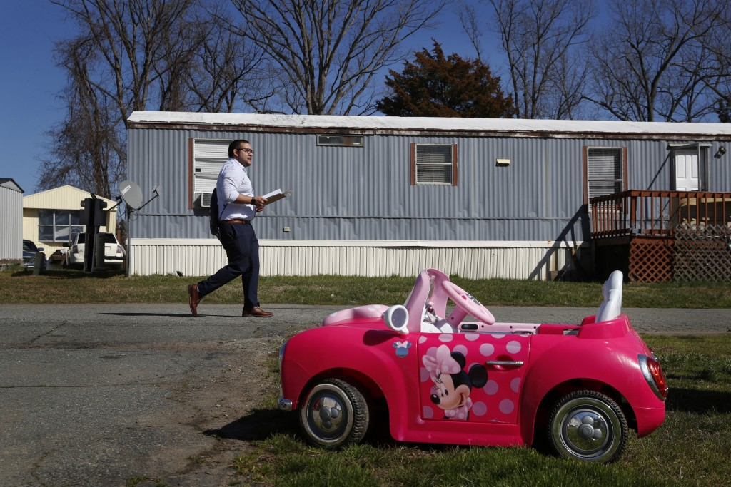 Ricky Hurtado, a Democratic candidate for the North Carolina state house, walks past a child's toy car as he canvasses in a largely Latino trailer com...