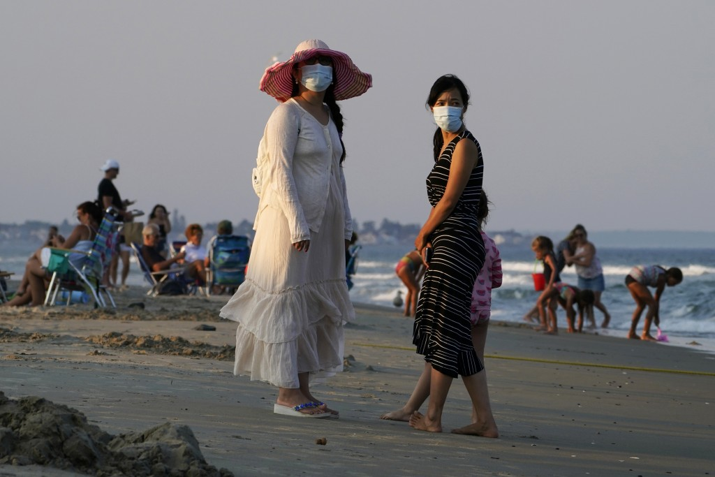 Women wear masks to help prevent the spread of coronavirus at the end of a beach day, Tuesday, Aug. 11, 2020, in Ogunquit, Maine. (AP Photo/Robert F. ...