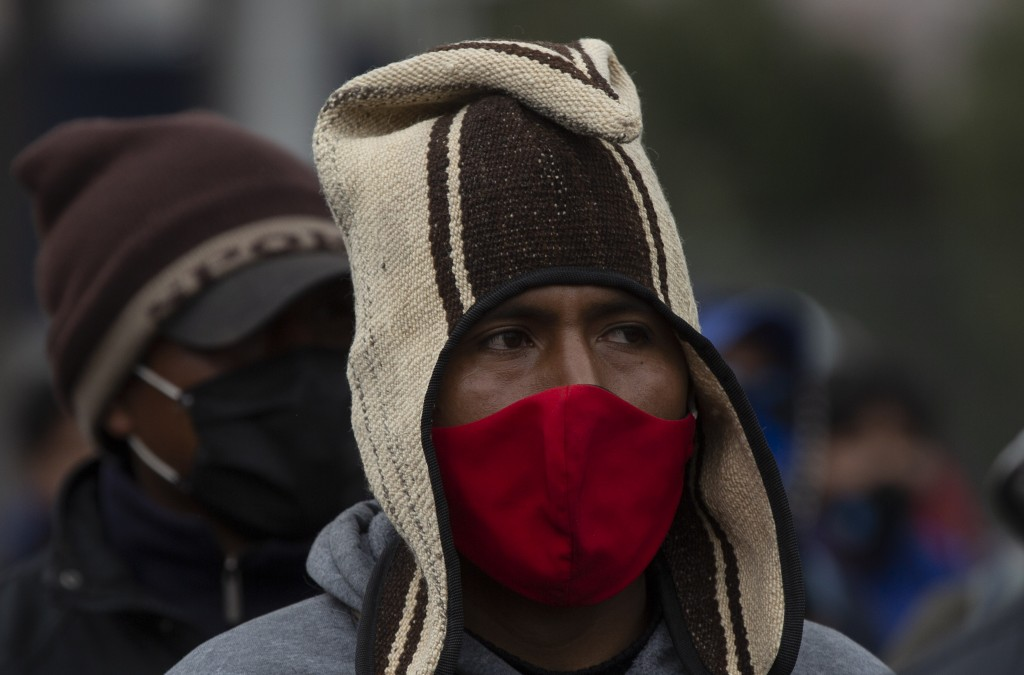 A demonstrator wearing a face a mask amid the COVID-19 pandemic, joins a protest against the postponement of the presidential election, in El Alto, Bo...