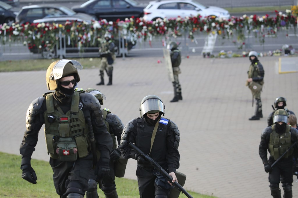 Police protect an area from opposition supporters protesting the election results as protesters encountered aggressive police tactics in the capital o...