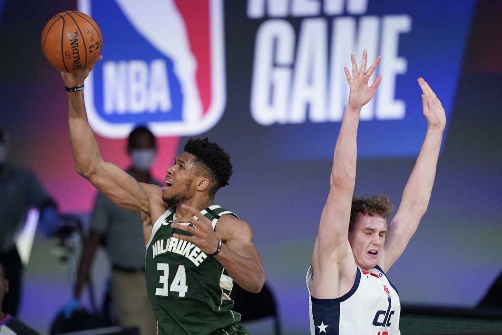 Milwaukee Bucks' Giannis Antetokounmpo (34) drives to the basket past Washington Wizards' Anzejs Pasecniks, right, during the first half of an NBA bas...