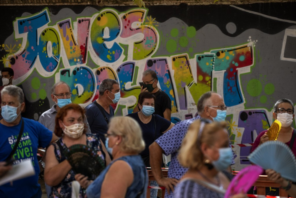 People wearing face masks queue up to be tested for COVID-19, at Vilafranca del Penedes in the Barcelona province, Spain, Monday, August 10, 2020. Spa...