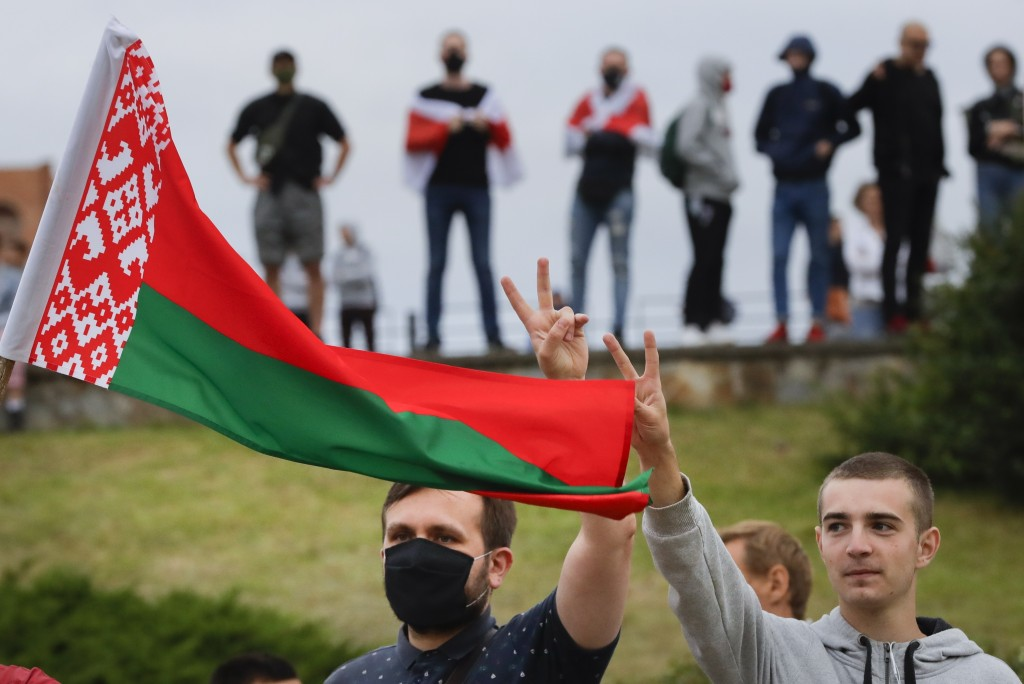 CORRECTING COUNTRY IN CAPTION TO BELARUS - People with Belarusian National flag gather in a street protesting the election results in Minsk, Belarus, ...