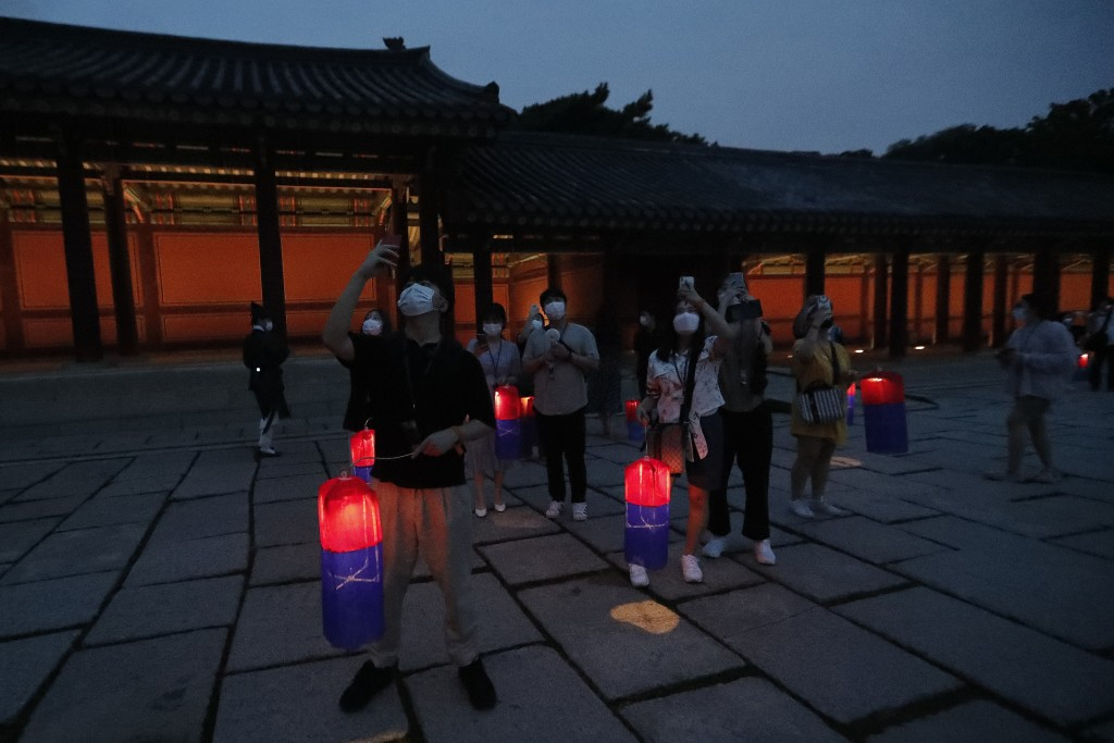 Visitors holding Korean traditional lanterns take pictures during the Moonlight Tour at Changdeokgung Palace in Seoul, South Korea, Thursday, Aug. 13,...