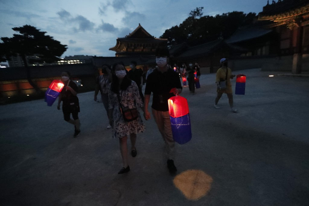 Visitors holding Korean traditional lanterns walk around during the Moonlight Tour at Changdeokgung Palace in Seoul, South Korea, Thursday, Aug. 13, 2...