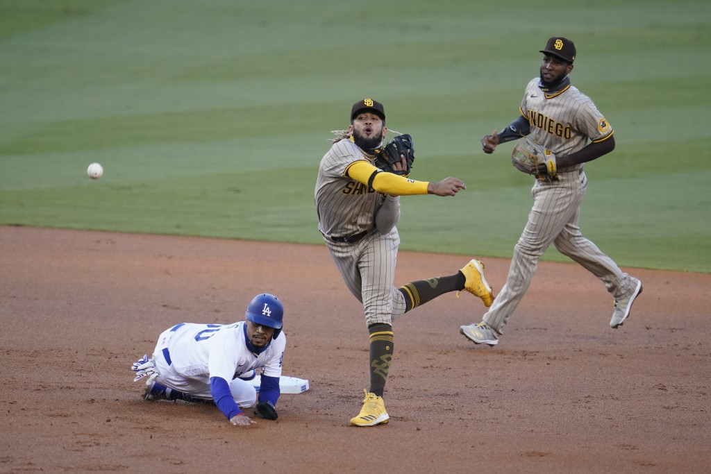 San Diego Padres shortstop Fernando Tatis Jr., center, completes a double play over Los Angeles Dodgers' Mookie Betts, left, on a ground ball from Cod...