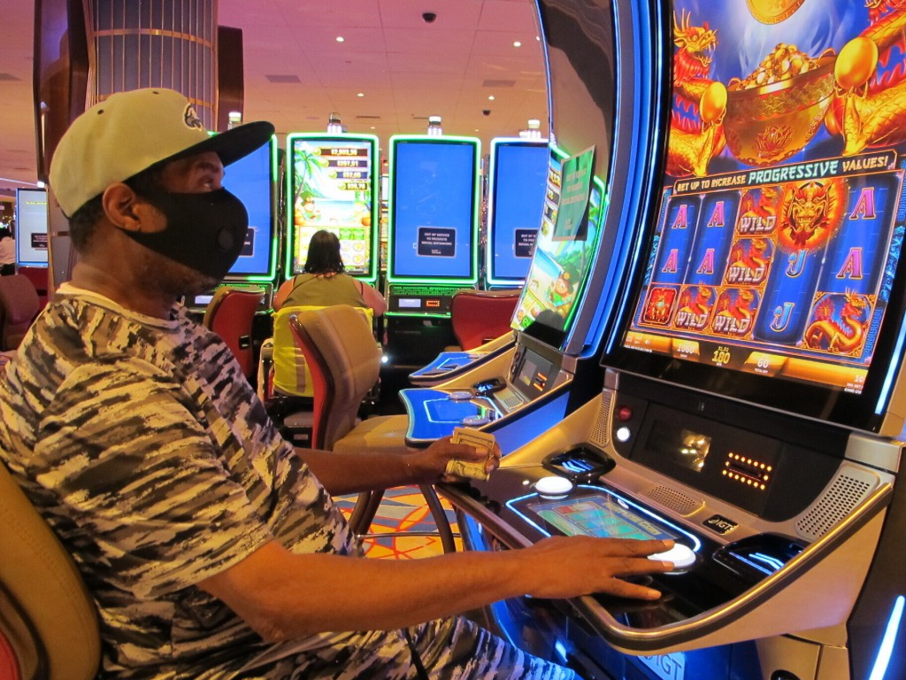 A gambler plays a slot machine at the Hard Rock Casino in Atlantic City N.J. on July 2, 2020, the day the casino reopened amid the coronavirus outbrea...