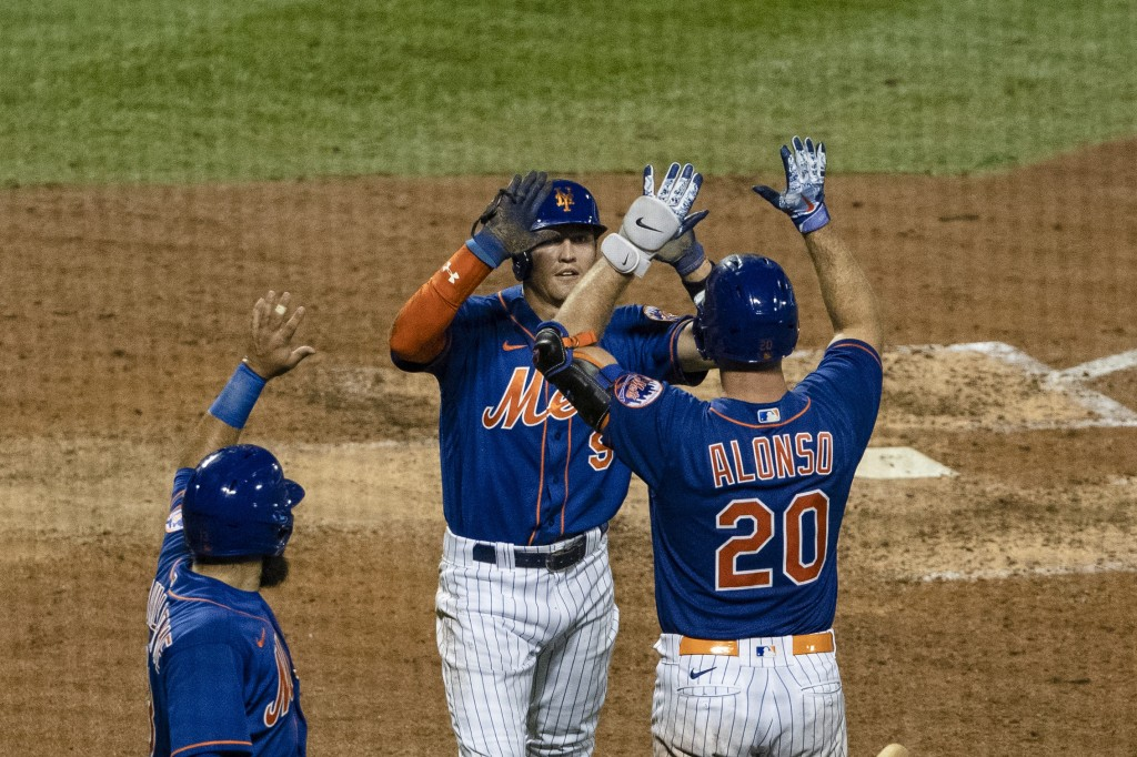 New York Mets' Luis Guillorme, left, celebrates with teammates Brandon Nimmo (9) and Pete Alonso (20) after a two-run double by Michael Conforto durin...
