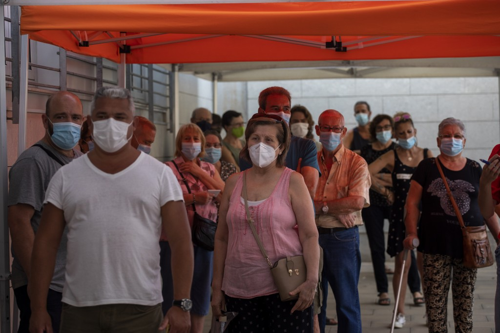 People wearing face masks queue up to be tested for COVID-19, outside a local clinic in Santa Coloma de Gramanet in Barcelona, Spain, Tuesday, Aug. 11...