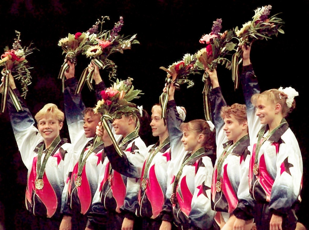 FILE - In this July 23, 1996, file photo, members of the United States women's gymnastics team wave to the crowd after being awarded their gold medals...