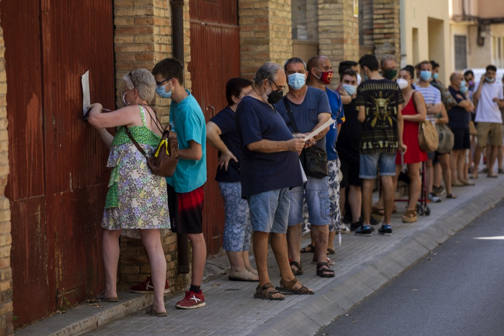 People wearing face masks queue up to be tested for COVID-19,  at Vilafranca del Penedes in the Barcelona province, Spain, Monday, Aug. 10, 2020. Spai...