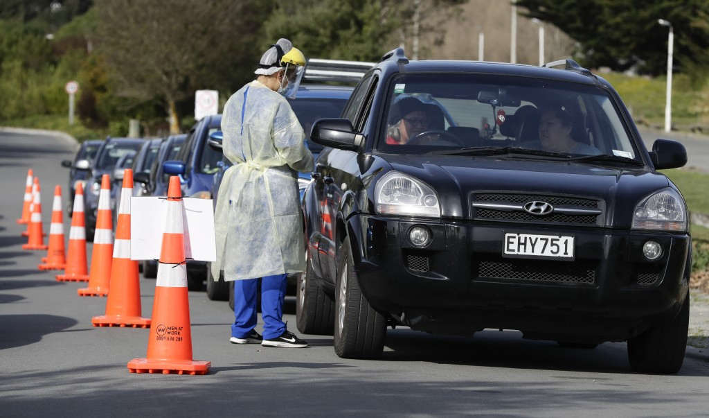 Medical staff prepare take a COVID-19 test from a visitor to a drive through community based assessment centre in Christchurch, New Zealand, Thursday,...