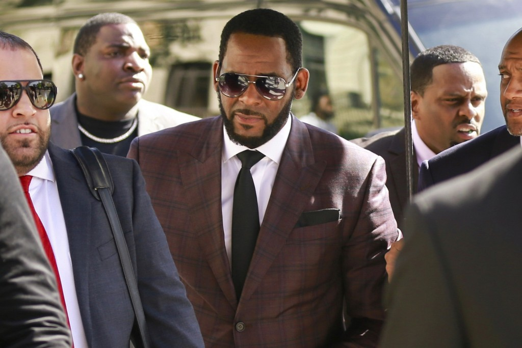 FILE - In this June 26, 2019 file photo, R&B singer R. Kelly, center, arrives at the Leighton Criminal Court building for an arraignment on sex-relate...