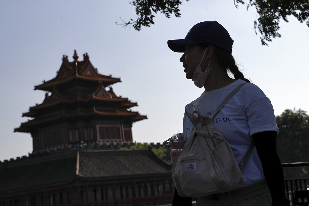 A woman puts down her face mask walks by the Turret of the Forbidden City in Beijing, Thursday, Aug. 13, 2020. New local cases in China fell into the ...